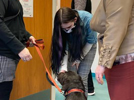 student greeting support dog