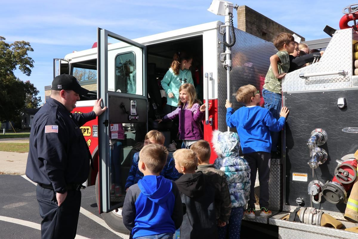Elementary students examining fire truck