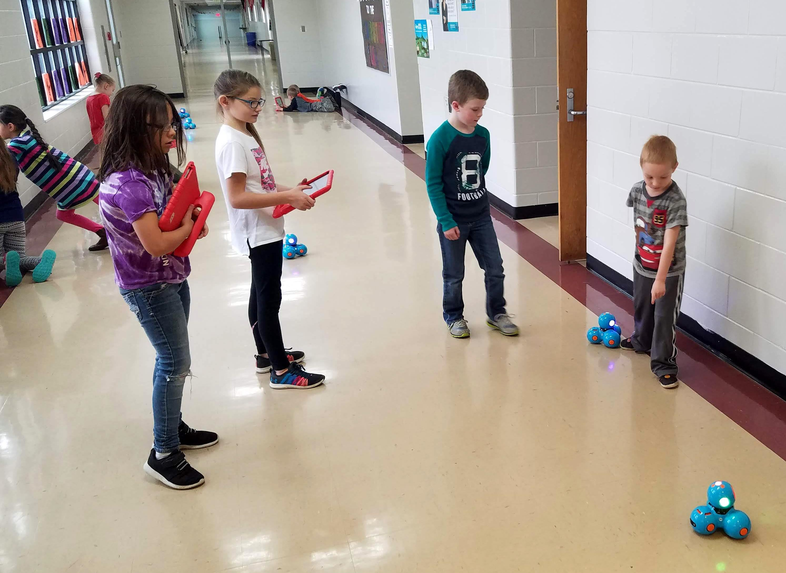 4 elementary students in school hall with small robots.