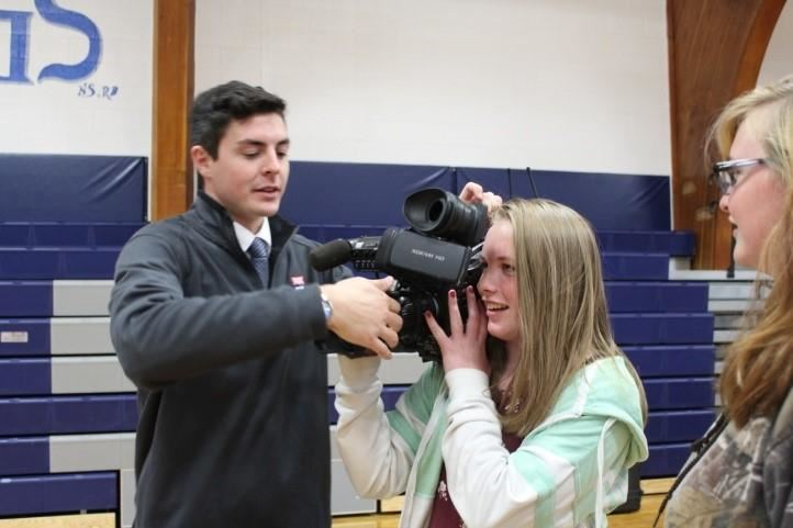 Man showing video camera to female student