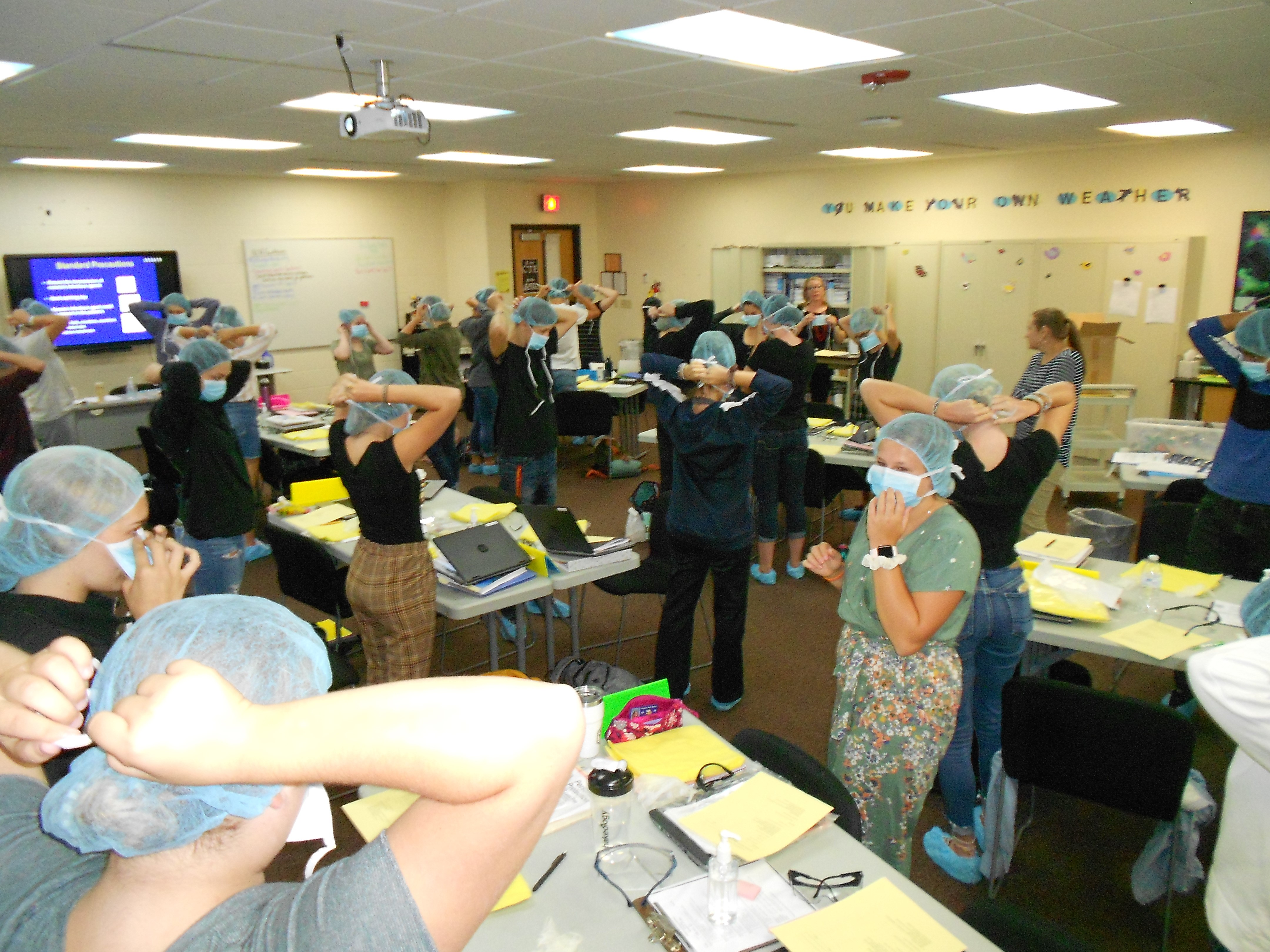 Students putting on gowns and gloves to get ready for training.